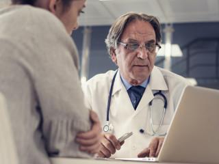 Starší doktor u počítače vysvětluje mladé pacientce její zdravotní stav.