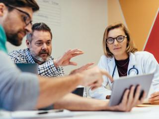 Skupina zdravotnických pracovníků s digitálním setkáním tablet v nemocniční zasedací místnosti. Zdravotnický personál během ranní porady.