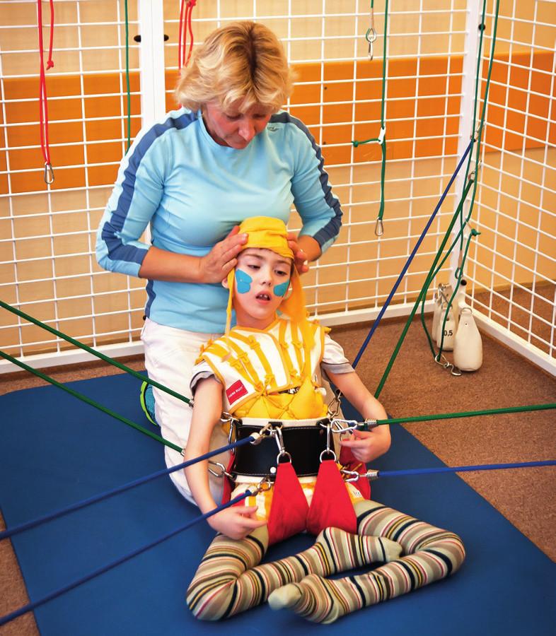 Ilustrační fotografie upevnění dítěte do systému kladek, závěsů a tahů pružných lan.