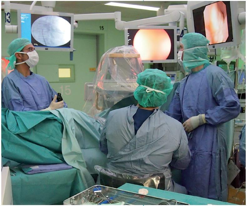 """Záběr z operačního sálu ze simultánního provedení levostranné fl exibilní ureteroskopie (stojící prof. O. Traxer) a perkutánní nefroskopie v poloze na zádech (""""supine position"""", sedící prof. J. de la Rosette). Výkon byl prováděn pro odlitkovou nefrolitiázu."""