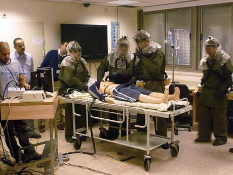 Cvičící v ochranných oděvech při zdravotnickém zásahu po použití nekonvenčních zbraní.