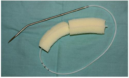Podtlakový systém zhotovený z Redonova drénu a sterilní polyuretanové mycí houby před zavedením do rány