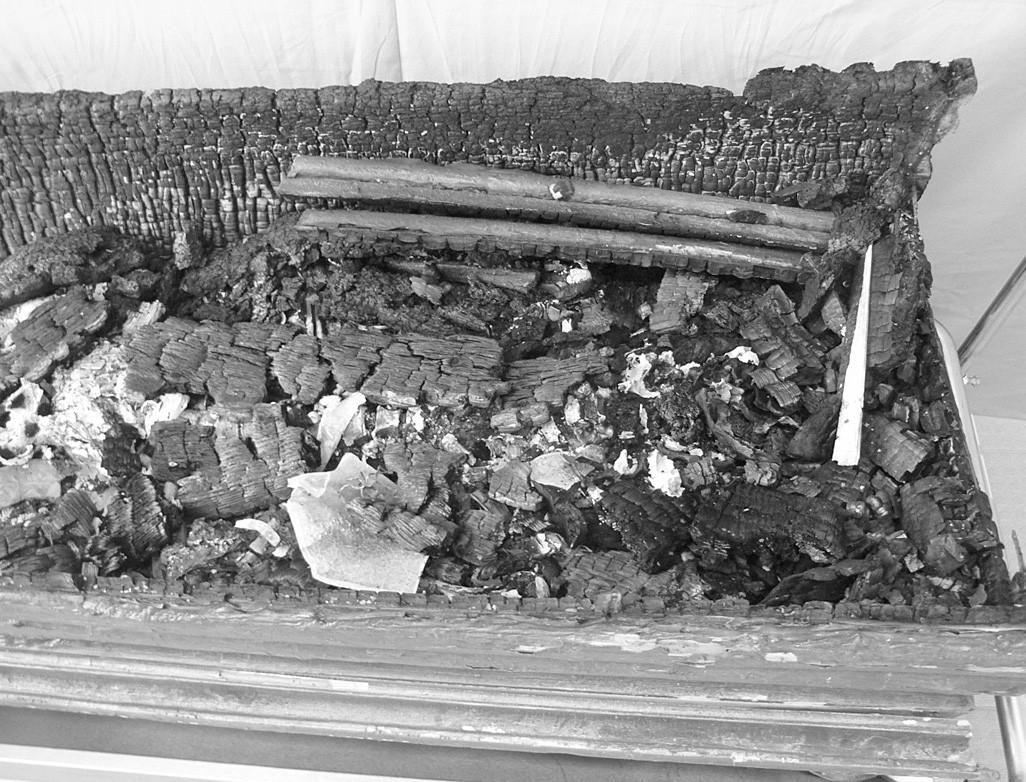 Horná časť rakvy: zvyšky zhoreného dreva, termicky poškodené kosti a fragmenty roztaveného skla.