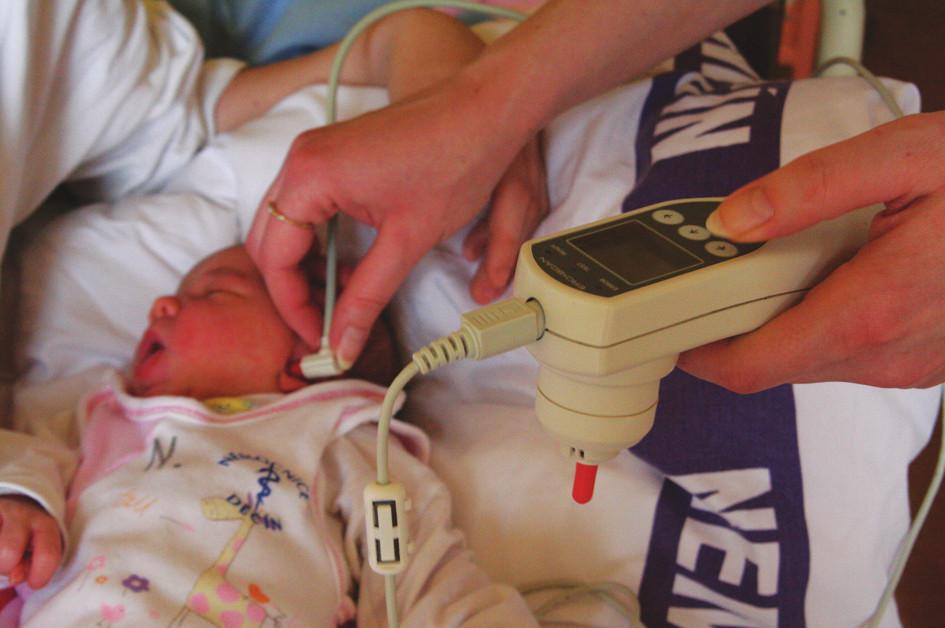 Vyšetření novorozence při použití ruční sondy s jednorázovou ušní koncovkou.