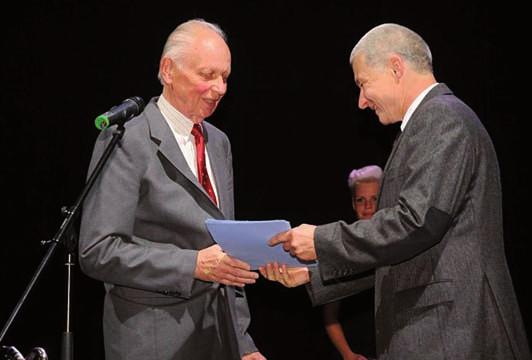 Ing. Bašák, personální fieditel Pražské plynárenské, zástupce sponzora, gratuluje MUDr. Sotorníkovi k udělení ceny