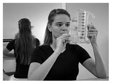 Pacientka cvičí s nádechovou pomůckou DHD Coach 2, která funguje na principu zpětné vazby a slouží tak k reedukaci dechového stereotypu. Fotografie byla pořízena s informovaným souhlasem pacientky.