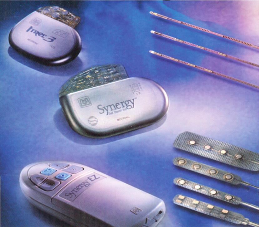 Dva druhy klasických (konvenčních) generátorů vlevo nahoře, perkutánní elektrody, v pravém horním rohu a chirurgické v pravém dolním rohu snímku. Vlevo dole je pacientský ovladač k ovládání přístroje po definitivní implantaci generátoru do podkoží.