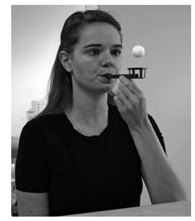 Plynulost a koordinaci svého výdechu pacientka kontroluje a řídí dle výšky vyfouknutého balónku s použitím výdechové pomůcky Flow-Ball. Fotografie byla pořízena s informovaným souhlasem pacientky.
